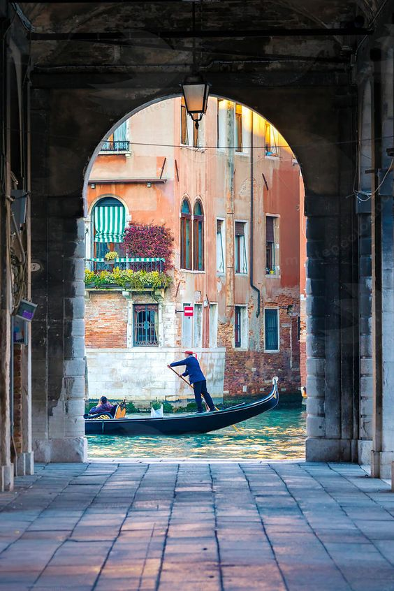 Italy, Veneto, Venice. Gondola passing on Grand canal seen from a colonnade